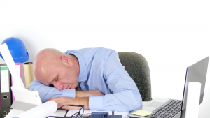 A picture of a person asleep on a desk